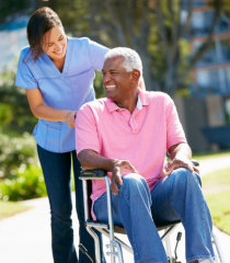 nurse and elderly man in wheelchair smiling